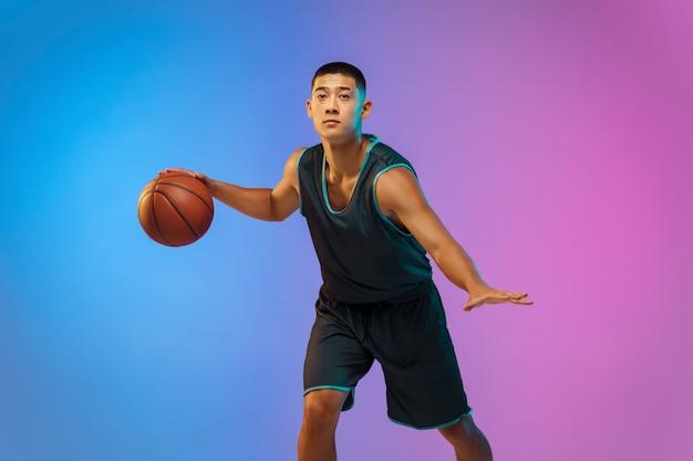 네온 불빛에 그라데이션 스튜디오 배경에 모션에서 젊은 농구 선수
