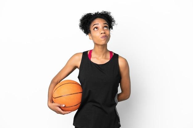 Латинская женщина молодой баскетболист, изолированные на белом фоне и глядя вверх