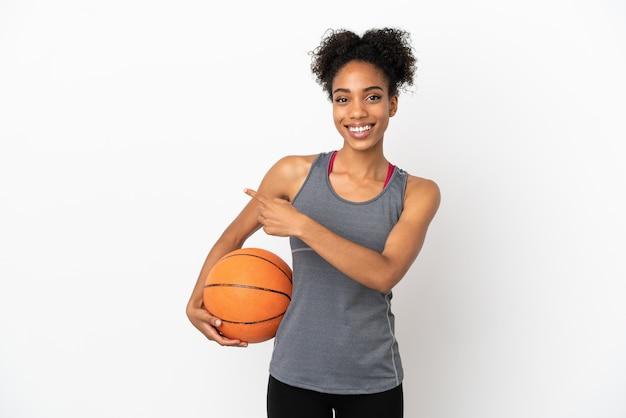 バスケットボールをし、側面を指している白い背景で隔離の若いバスケットボール選手ラテン女性