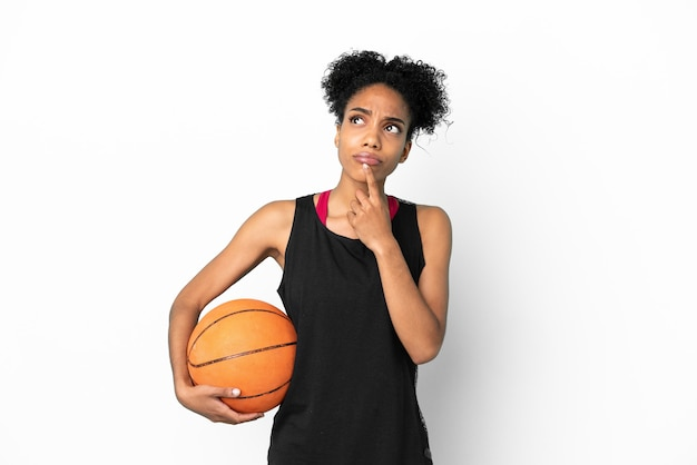 Young basketball player latin woman isolated on white background having doubts while looking up