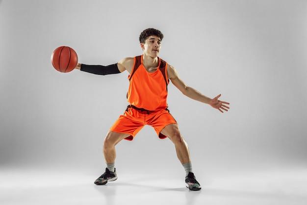 Молодой баскетболист команды носить спортивную подготовку, практикуя в действии, движение в беге, изолированные на белом фоне.