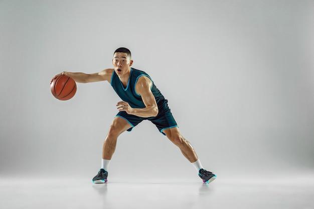 スポーツウェアのトレーニングを身に着けているチームの若いバスケットボール選手、アクションの練習、白い壁に隔離された実行の動き。スポーツ、運動、エネルギー、ダイナミックで健康的なライフスタイルのコンセプト。