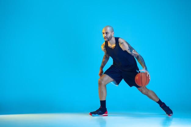운동복 훈련을 입고 팀의 젊은 농구 선수, 행동, 네온 불빛에 파란색 배경에 고립 된 모션 연습. 스포츠, 운동, 에너지 및 역동적이고 건강한 라이프 스타일의 개념.