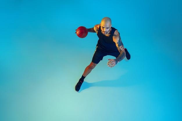 운동복 훈련을 입고 팀의 젊은 농구 선수, 네온 불빛에 파란색 벽에 동작 연습
