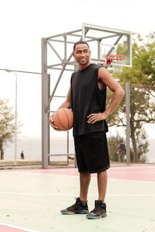壁にバスケットボールのフープと通りに立っている若いバスケットボール選手