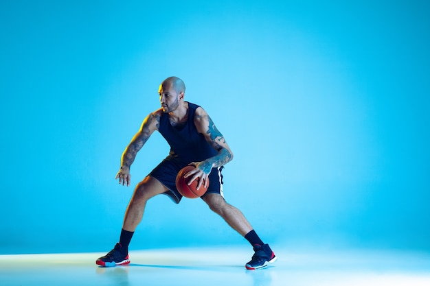 Young basketball player of team wearing sportwear training, practicing in action, isolated on blue wall in neon light