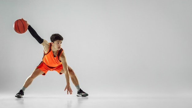 Young basketball player of team wearing sportwear training, practicing in action, motion in run isolated on white background.