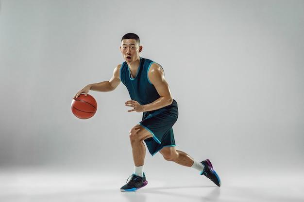 Giovane giocatore di basket della squadra che indossa la formazione di abbigliamento sportivo, praticando in azione, movimento in esecuzione isolato sul muro bianco. concetto di sport, movimento, energia e stile di vita dinamico e sano.