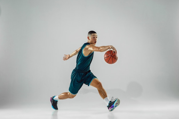 Young basketball player of team wearing sportwear training, practicing in action, motion in run isolated on white wall. concept of sport, movement, energy and dynamic, healthy lifestyle.