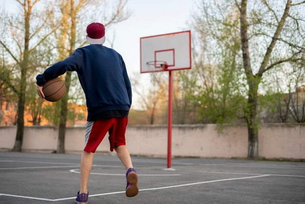 Young basketball player training to dribble outdoor on the asphalt court