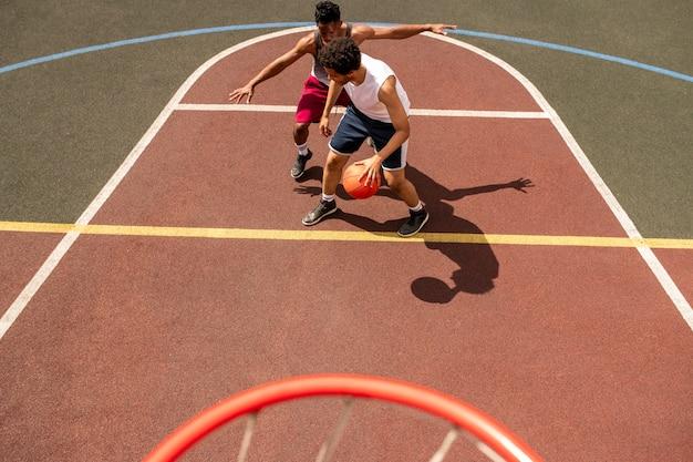 Молодой баскетболист пытается защитить мяч от атаки соперника во время игры на открытой площадке