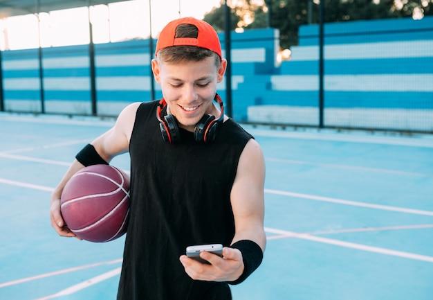ボールを持った若いバスケットボール選手が携帯電話を見て、休憩しながら微笑む
