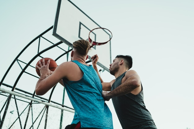 Young basketball players playing one-on-one on outdoor court. sport and basketball concept.