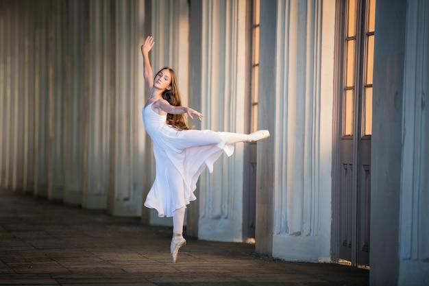 長いルーズな髪の長い白いスカートの若いバイエルナは、ポアントで優雅なポーズで立っています