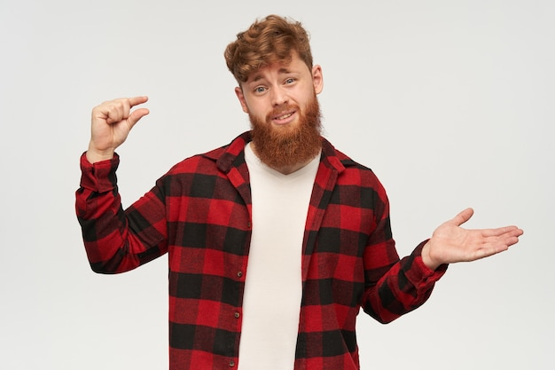 Young beaded man with big red beard shows something small with his hand, looking at front with sad and confused facial expression