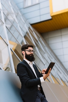 Young beard businessman leaning on wall looking at smartphone