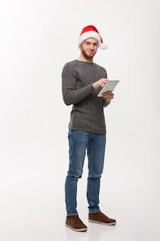 Uomo bello della giovane barba che lavora sulla tavoletta digitale su bianco