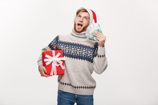 Giovane uomo con la barba in possesso di un regalo di natale e denaro su bianco