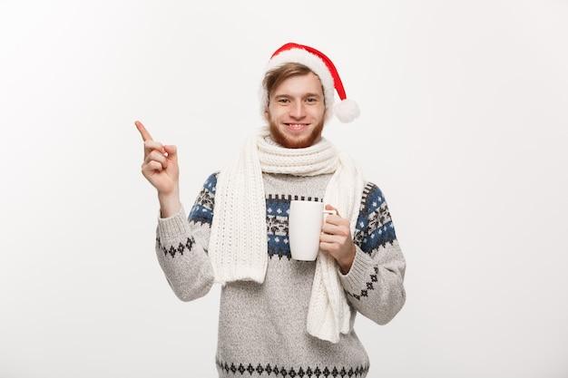 Молодой бородатый мужчина в свитере и шляпе санта-клауса держит чашку горячего кофе, указывая рукой на бок на белом