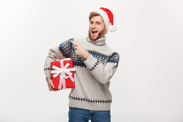 Young beard man in sweater holding box and pointing hand at side