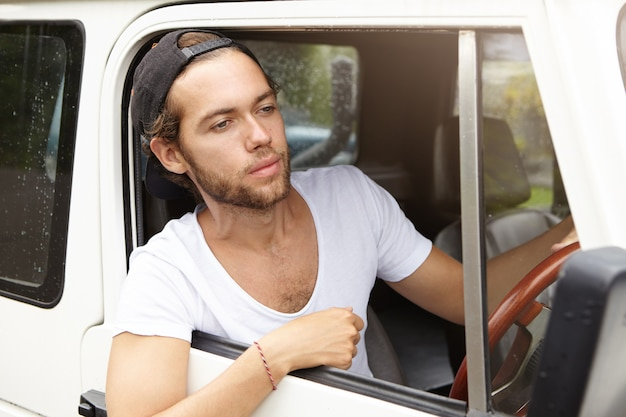 Young bearded adventurer wearing black snapback driving his white suv, going to safari trip, sticking his head out of open window, having tired and unhappy look