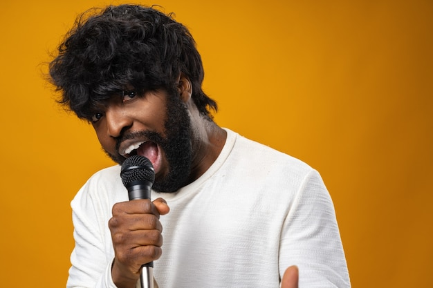 Молодой бородатый афро-американский мужчина поет в микрофон на желтой поверхности