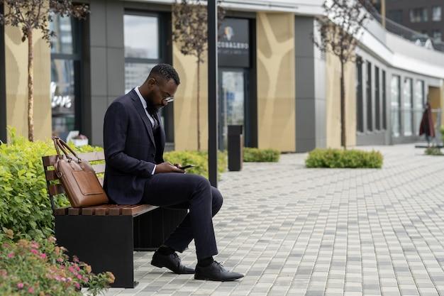 스마트폰에서 스크롤하는 젊은 수염된 아프리카 사업가