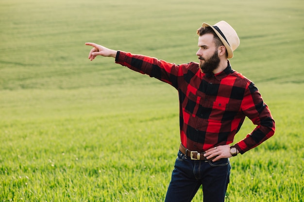 Young bearded agronomist standing in cultivated wheat crops field
