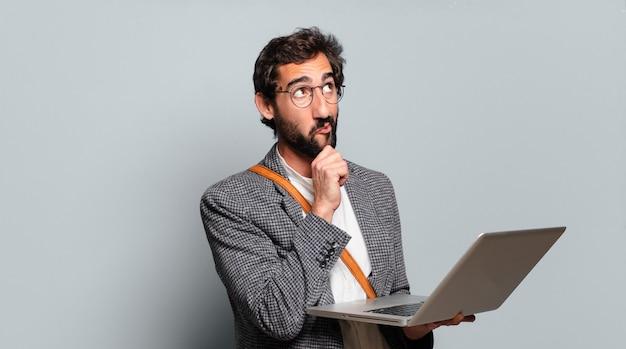 Молодой бородатый и сумасшедший бизнесмен с ноутбуком