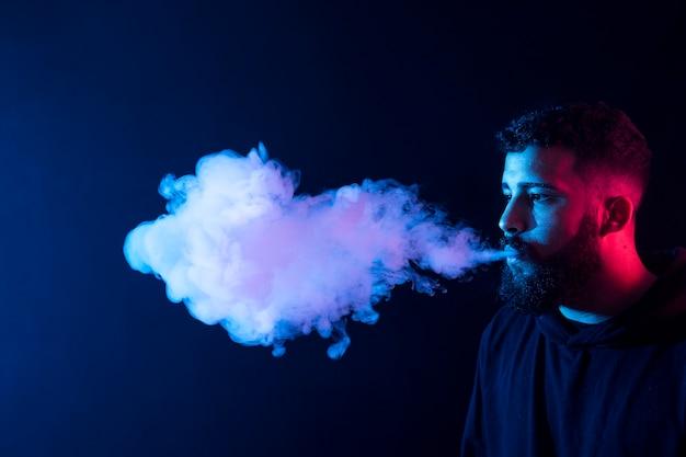 젊은 수염 아랍 남자 흡연 vape 및 컬러 조명으로 트릭을하고. 공간을 복사하십시오.