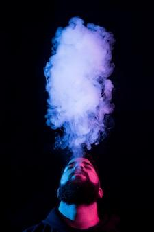 젊은 수염 아랍 남자 흡연 vape 및 컬러 조명으로 트릭을하고. 세로