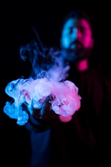 Young bearded arab man smoking vape and doing tricks with colored lights.