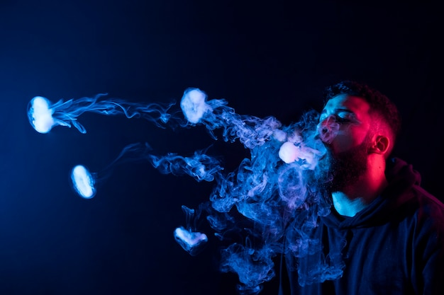Young bearded arab man smoking vape and making smoke rings with colored lights. copy space.