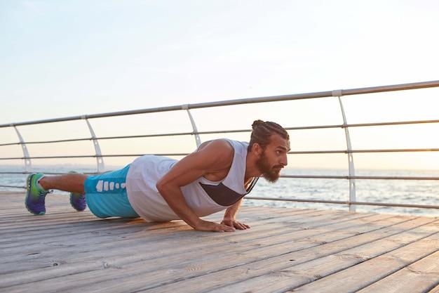 Giovane gay atletico barbuto che fa flessioni, tiene l'asse, fa esercizi mattutini in riva al mare, si riscalda dopo la corsa.