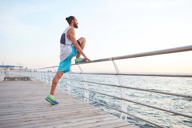 Young bearded attracive guy doing morning exercises by the sea, warm-up after run, stretching for legs, leads healthy active lifestyle. fitness male model.