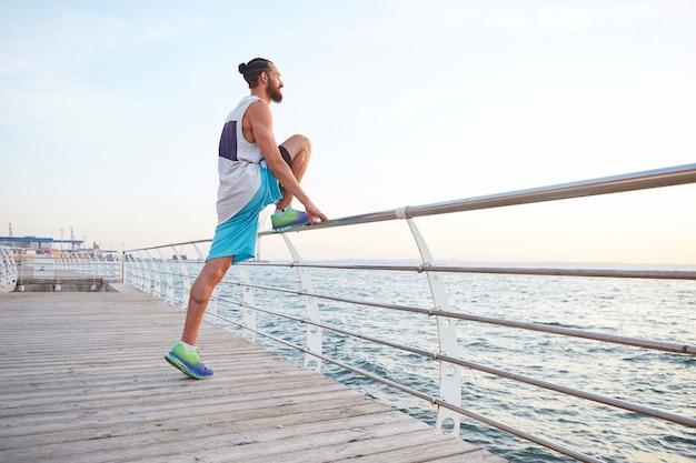 Giovane ragazzo barbuto attraente facendo esercizi mattutini in riva al mare, riscaldamento dopo la corsa. stretching per le gambe,