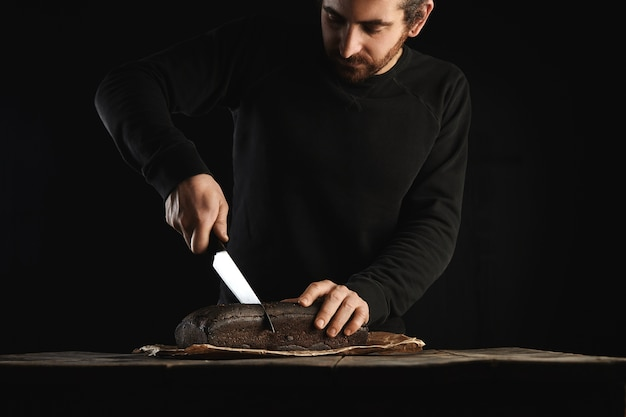 Young bearded baker man in black sweatshot uses big chief knife to slice homemade luxury bread from figs and rye in craft paper on rustic wooden table isolated on black