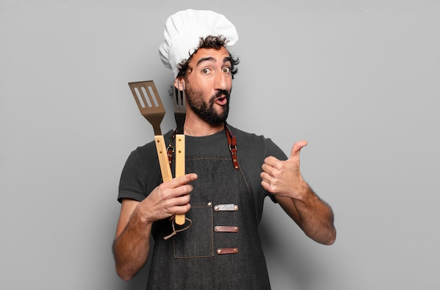 キッチンツールを保持している若いひげを生やしたバーベキューシェフ