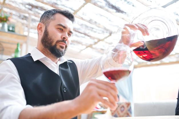 Молодой бородатый бармен или сомелье наливает красное вино в бокал во время работы в погребе или баре