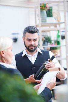 Young bearded bartender giving characteristics of new sort of wine in bottle to cavist while both working in cellar