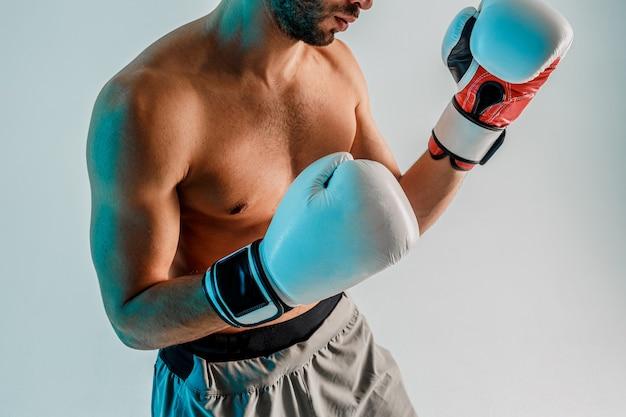 Молодой бородатый боксер занимается боксом. частичный вид спортсмена в боксерских перчатках. изолированные на бирюзовом фоне. студийная съемка