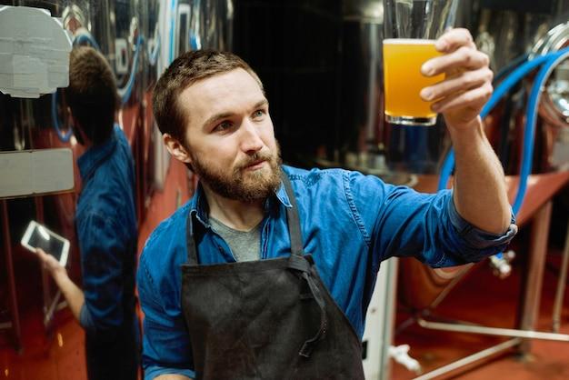 Молодой бородатый мастер пивоварни в спецодежде, глядя на стакан пива в руке, оценивая его визуальные характеристики во время работы на заводе
