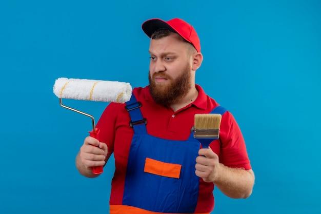 Giovane barbuto uomo costruttore in uniforme da costruzione e cappello tenendo il rullo di vernice e pennello guardando il rullo con espressione scettica sul viso
