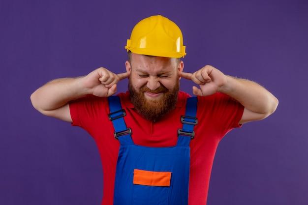 Uomo giovane barbuto costruttore in uniforme da costruzione e casco di sicurezza che copre le orecchie con le dita con espressione infastidita per il rumore del suono forte su sfondo viola