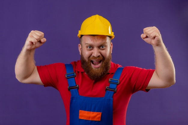 Young bearded builder man in construction uniform and safety helmet crazy happy clenching fists shouting rejoicing his success over purple background