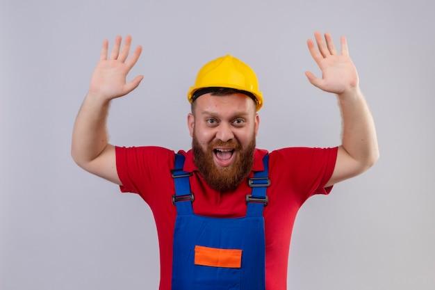 Uomo giovane barbuto costruttore in uniforme da costruzione e casco di sicurezza emotivo ed uscito alzando le mani in segno di resa