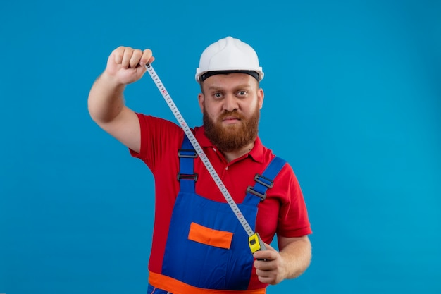 Young bearded builder man in construction uniform and safety helmet holding measurement tape with serious face