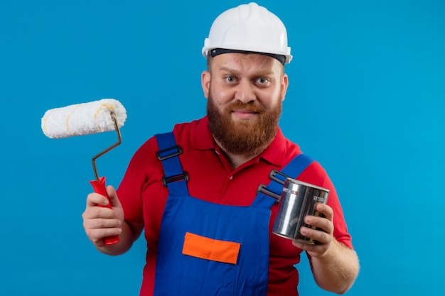 Young bearded builder man in construction uniform and safety helmet holding paint roller and can with unhappy face