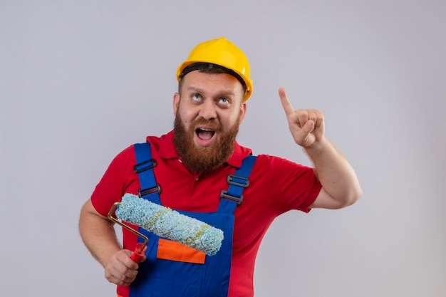 Young bearded builder man in construction uniform and safety helmet holding paint roller pointing index finger up shouting