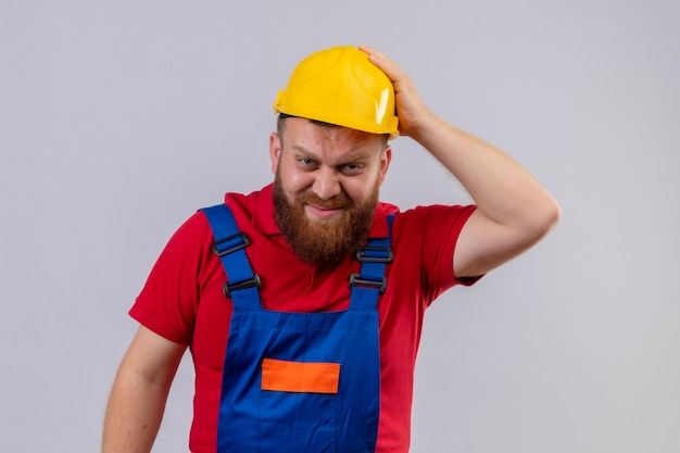Young bearded builder man in construction uniform and safety helmet looking at camera confused and very anxious with hand on head for mistake